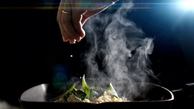 en kock häller salt på de kinesiska nudlarna i pannan. slow motion. - frying pan bildbanksvideor och videomaterial från bakom kulisserna
