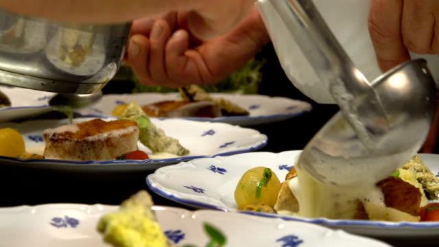 vídeos de stock e filmes b-roll de chef pours sauce fish dish on restaurant's kitchen - bacalhau