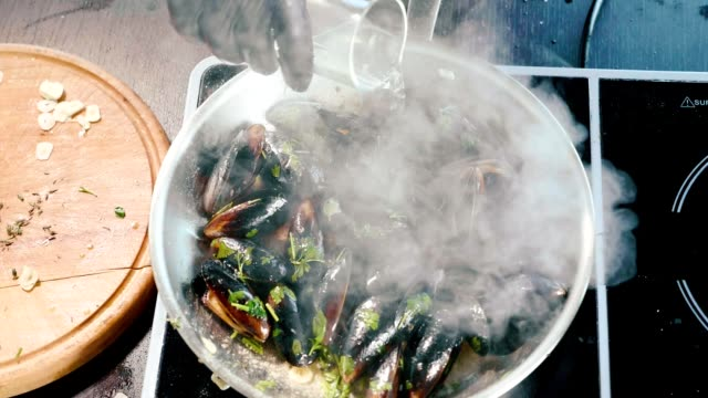 Chef pours wine in frying pan with hissing mussels and sets fire by gas burner