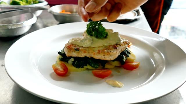 chef preparing chicken steak on white dish video