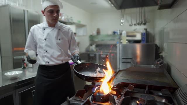 商業キッチンのガスストーブバーナーのフライパンでフランベの食事を準備するシェフ - 料理人点の映像素材/bロール