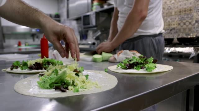 シェフがケータリング用の料理を準備しています。ベジタリアンブリトー食べる準備ができて - ベジタリアン料理点の映像素材/bロール