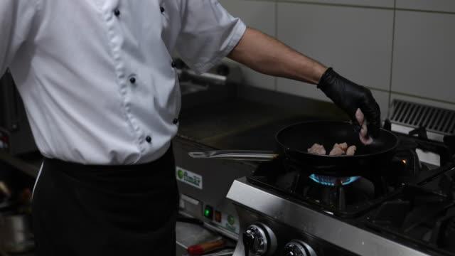 chef preparing meal at commercial kitchen - rękawiczka filmów i materiałów b-roll