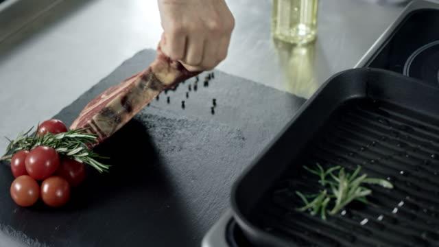 vídeos de stock e filmes b-roll de chef preparing meat at griddle. closeup man hands putting steak at grill. - meat texture