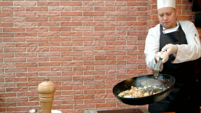 Chef preparing paella with swafood, mixing the dish with flying pan video