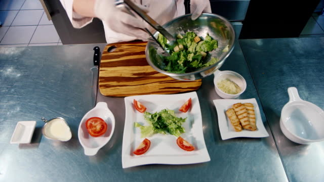Chef preparing salad Caesar, in the frame only hands visible video