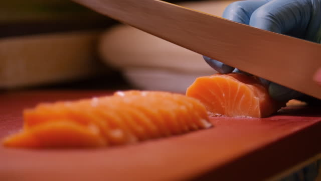 chef preparing salmon shushi. slicing salmon into pieces ready for shushi buffet night in a restaurant. - sashimi video stock e b–roll