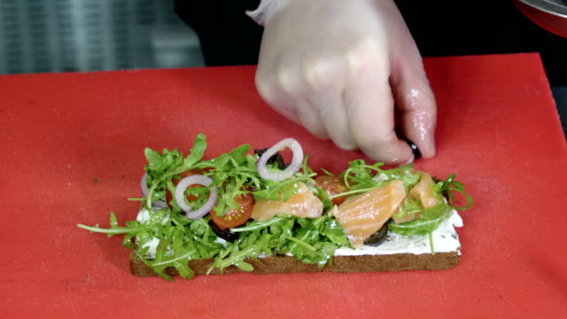 Chef preparing sandwich with rye bread, salmon, cheese, vegetables and herbs. 4K