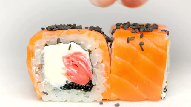 chef presentation of luxury japan restaurant sushi rolls Otary maki with fresh raw salmon, cheese ginger pink and tobiko caviar rotating on white video