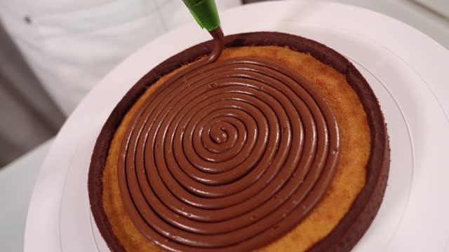 vídeos de stock e filmes b-roll de chef puts delicious chocolate cream on cake top on stand - bolo rainha