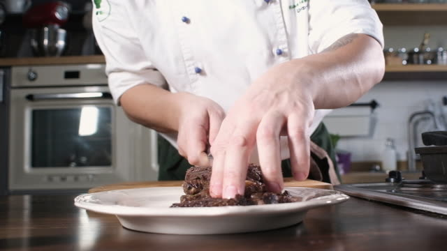 chef puts fried beef tenderloin cut into slices on plate. cooking in the kitchen - chef triste video stock e b–roll