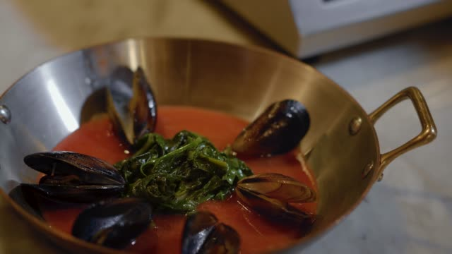Chef puts leaves and mussels in deep aluminium pan with handles with red sauce inside.