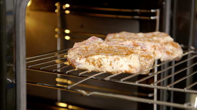 Chef puts ribeye pork chops on roasting rack into the oven with grill video