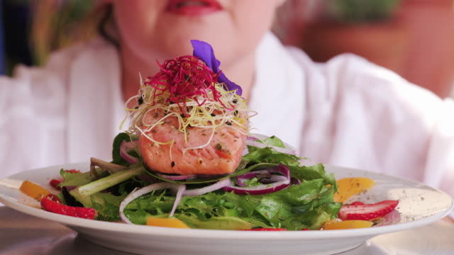 Chef putting finishing touches to a beautifully prepared pink salmon salad video