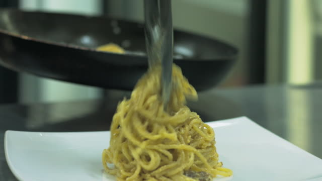 Chef putting italian pasta or spaghetti on dinner plate Young woman in restaurant kitchen is putting pasta from frying pan on dinner dish kitchen utensil stock videos & royalty-free footage