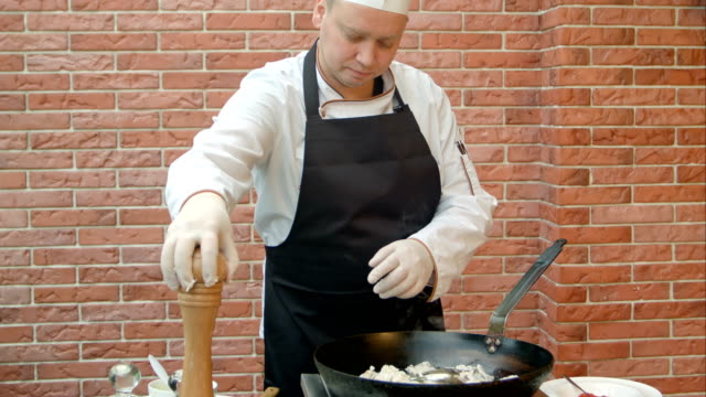 Chef putting salt and pepper to the pan for cooking seafood video