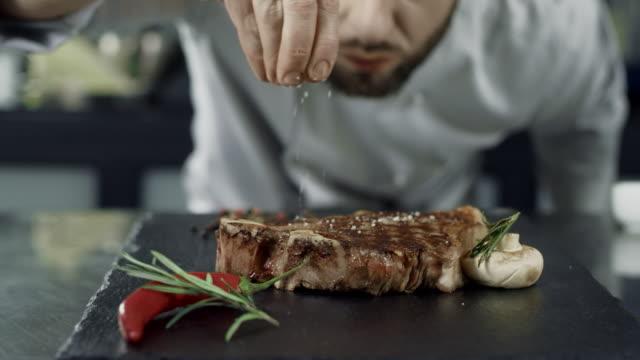 シェフの塩は鉄板で肉を揚げます。クローズアップマン手ソルトステーキスローモーション。 - 料理人点の映像素材/bロール