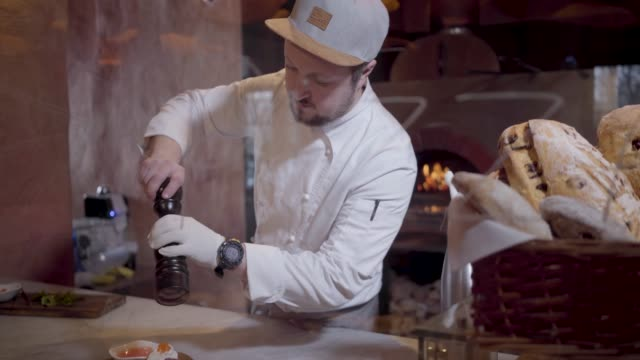 Chef salting a delicious mouth-watering sandwich.