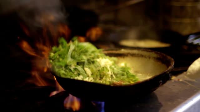 Chef sautés vegetables over a flame - CU, slow motion video