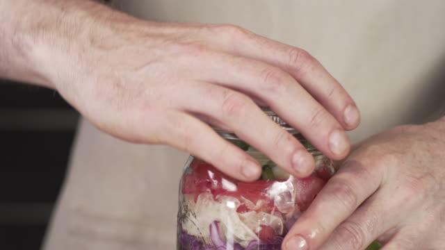 kocken skruva locket på stora mason jar sallad - konserveringsburk bildbanksvideor och videomaterial från bakom kulisserna