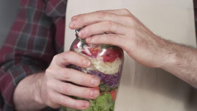 chef screwing lid onto large mason jar salad - coperchio video stock e b–roll