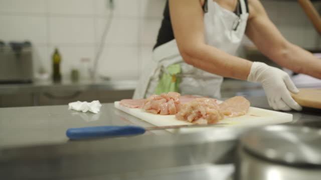 vídeos y material grabado en eventos de stock de chef condimentando pechugas de pollo picadas con polvo de cayena en la cocina comercial - cayena guindilla roja