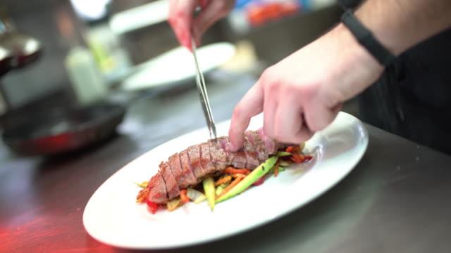 Chef serving sliced steak meal. video