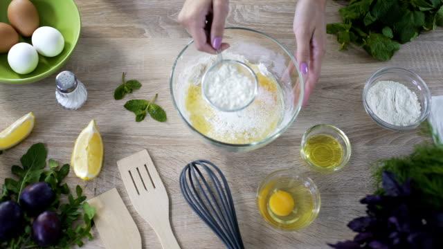 vidéos et rushes de chef de tamisage de farine dans le bol en verre avec des œufs avant vue de pétrissage, top - recette