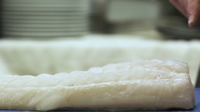 vídeos de stock e filmes b-roll de a chef slicing a cod fish in a kitchen of a restaurant. we can only see the hands of the cook cutting the raw fish - close-up view - cooking and food concept - cod