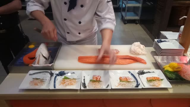 chef slicing and cutting salmon fish for cooking in kitchen - sashimi video stock e b–roll