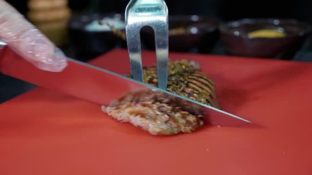 Chef slicing cooked pork steak at commercial kitchen video