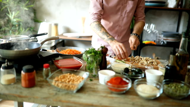 chef slicing mushrooms on wooden chopping board - przygotowywać jedzenie filmów i materiałów b-roll