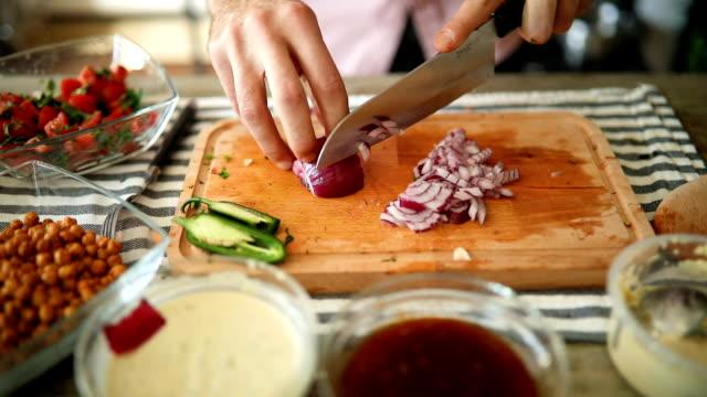 vídeos de stock, filmes e b-roll de chef que corta a cebola na placa de copping de madeira - rústico