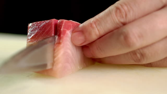vídeos y material grabado en eventos de stock de chef cortando un poco de sashimi hamachi en el bar de cocina en el restaurante japonés - cortar en trozos preparar comida