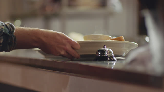 chef slides plates on kitchen counter, rings bell and male waiter picks up food to deliver to customers - restaurang bildbanksvideor och videomaterial från bakom kulisserna