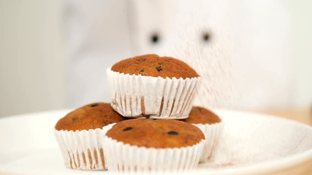 kocken strössel choklad pulver på cupcake, slowmotion. - confetti bildbanksvideor och videomaterial från bakom kulisserna