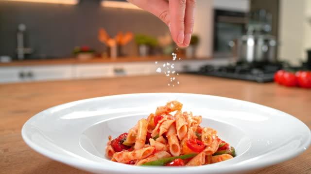 vídeos de stock, filmes e b-roll de slo mo ds chef polvilhando queijo em cima de macarrão - comida italiana