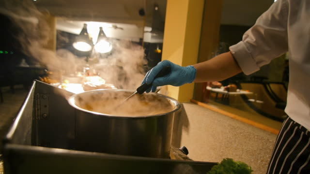 Chef stirring hot soup for customers. Slow motion steam. Buffet dinner.