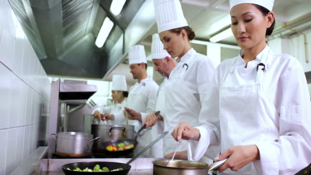chef stirring sauce smiling at camera - busy restaurant kitchen stock videos & royalty-free footage