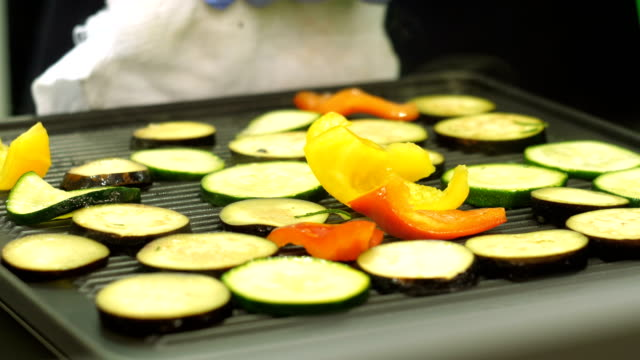 Chef takes a baking sheet with vegetables video