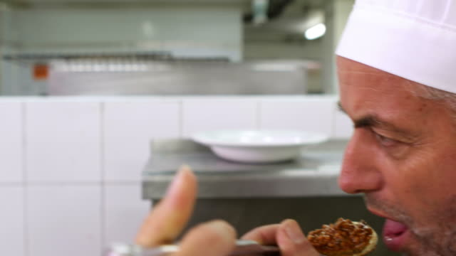 Chef tasting colleagues sauce and smiling at camera video