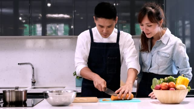 Chef teaching woman for cutting vegetable