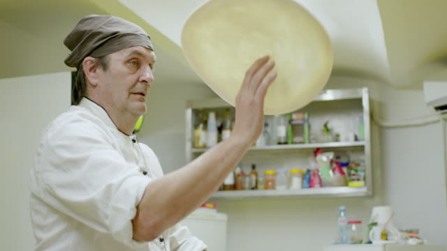 chef throwing pizza dough in the air with one hand - impasto video stock e b–roll