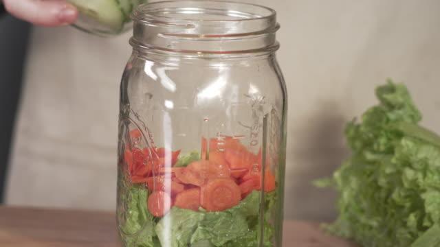 kocken toppning färska mason jar sallad med mogna gurkskivorna - konserveringsburk bildbanksvideor och videomaterial från bakom kulisserna