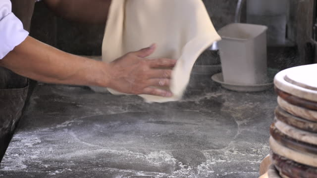 vídeos de stock e filmes b-roll de chef tossing pizza dough, skillful of chef preparing for cooking a pizza - pizza