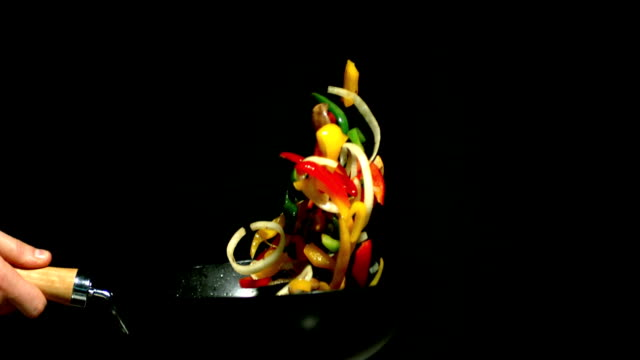 Chef tossing vegetables in wok side view on black background Chef tossing vegetables in wok side view on black background in slow motion stir fried stock videos & royalty-free footage