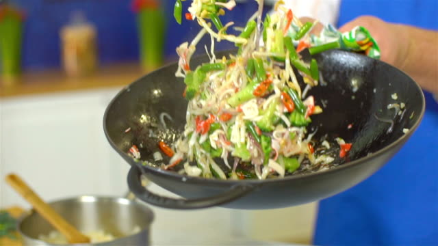 Chef tossing vegetables in wok, slo mo Chef tossing vegetables in wok, slo mo stir fried stock videos & royalty-free footage