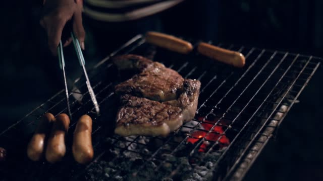 Chef turning meat on the grill with tongs, slow motion video