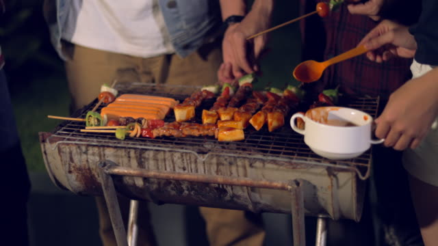 Chef turning meat on the grill with tongs video