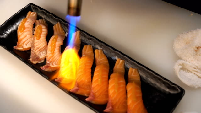 Chef using a flaming torch burn salmon sushi video